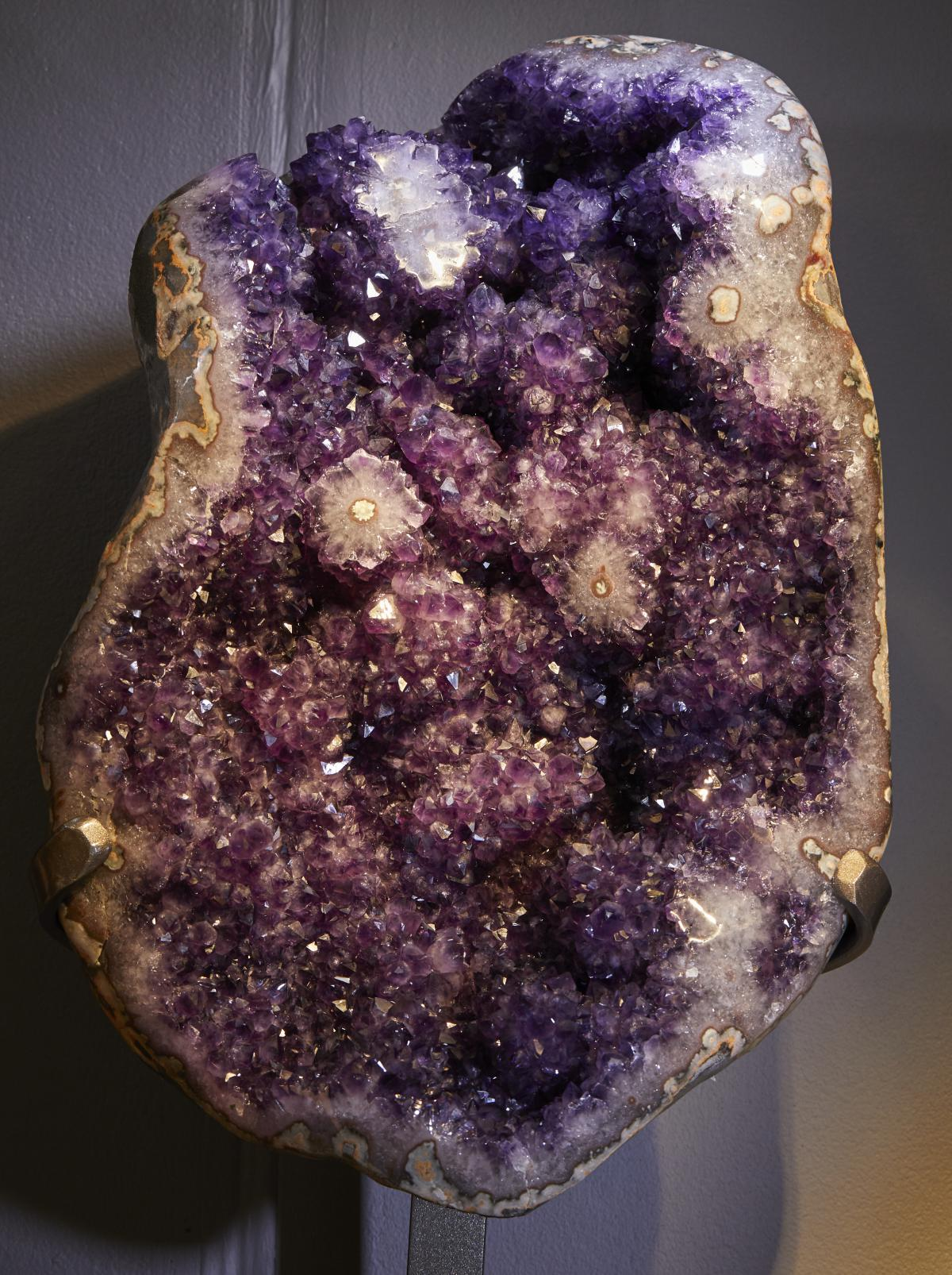A LARGE AMETHYST CLUSTER WITH STALACTITES ON METAL